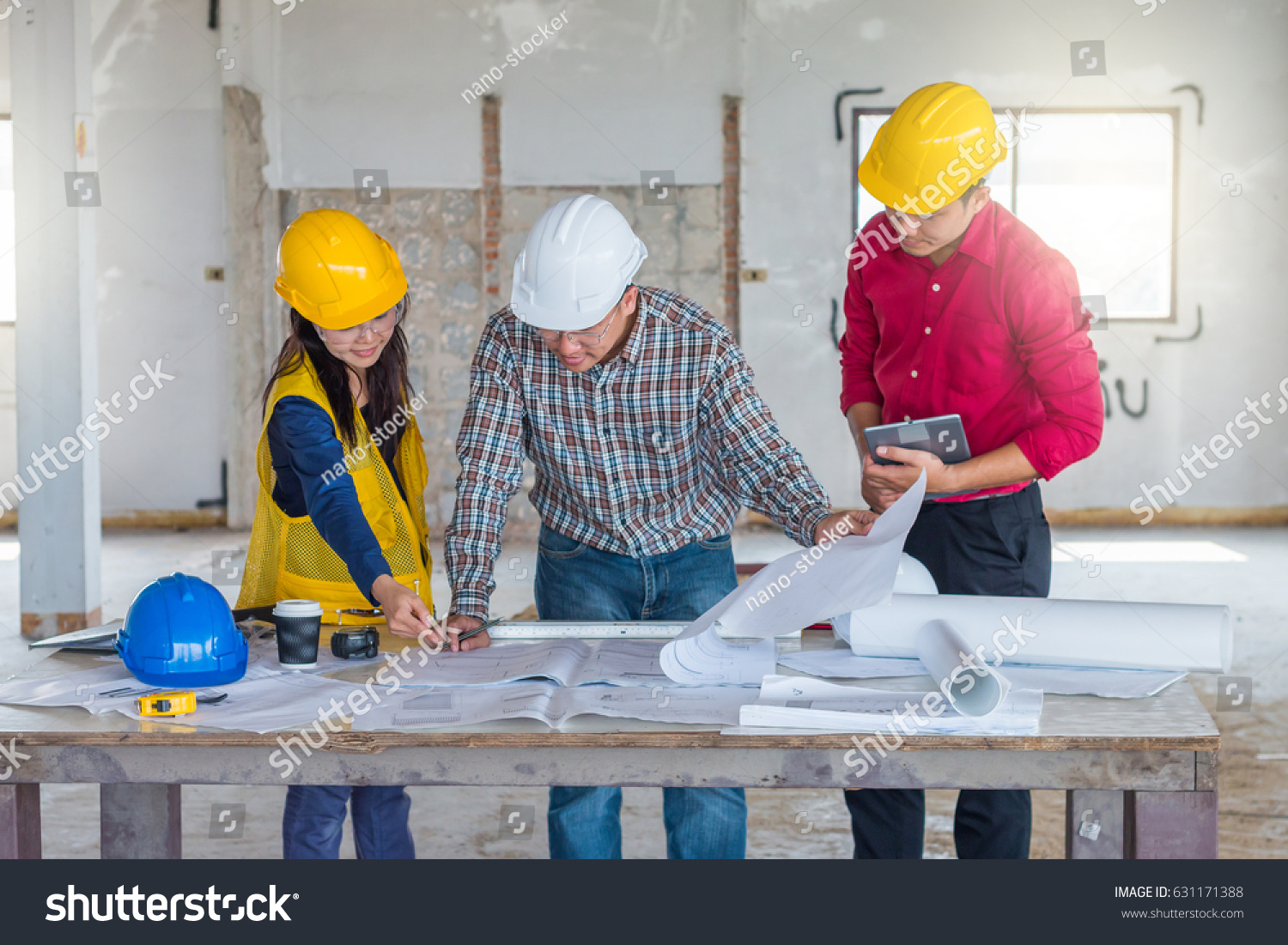 Group engineer checking blueprint on table stock photo image group of engineer checking the blueprint on the table and talking about construction project with commitment malvernweather Images