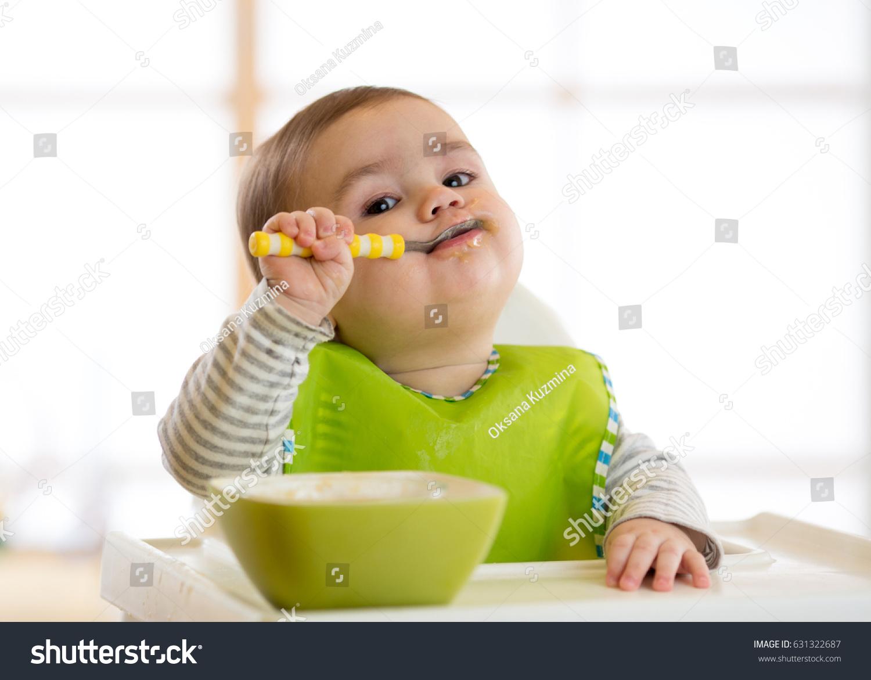Happy infant baby boy spoon eats itself #631322687