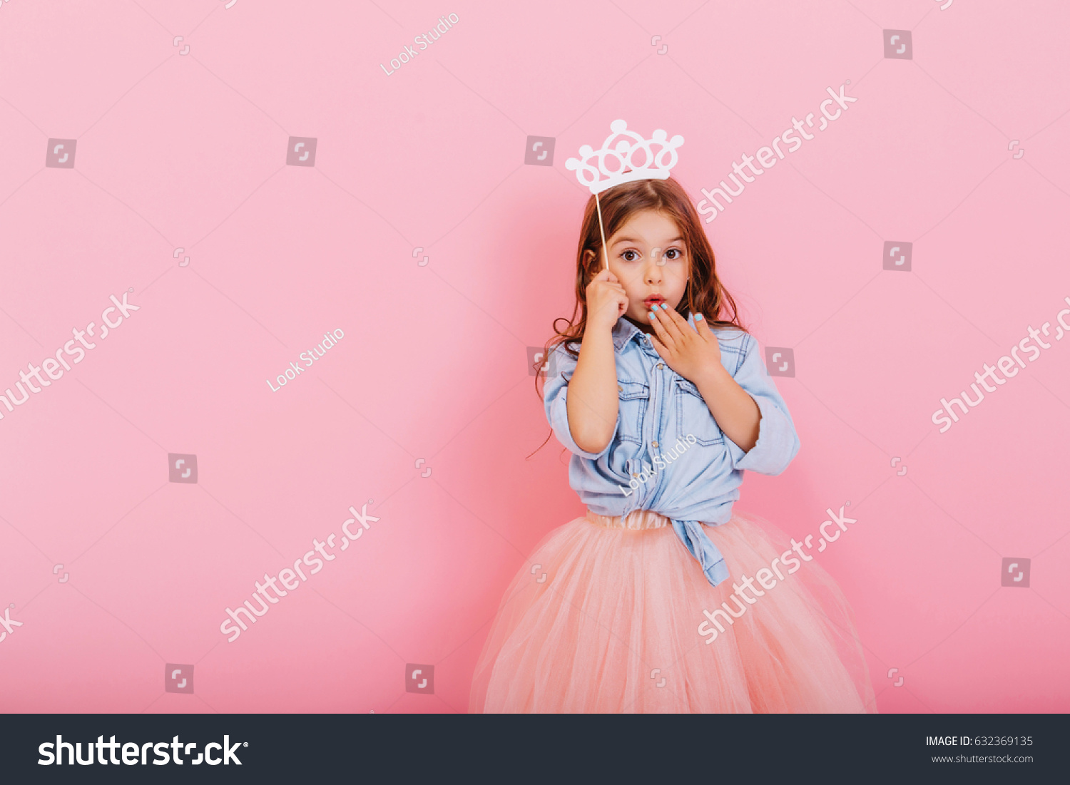 Surprised pretty young girl in tulle skirt with crown on head expressing isolated on pink background. Amazing cute little princess at carnival. Place for text #632369135