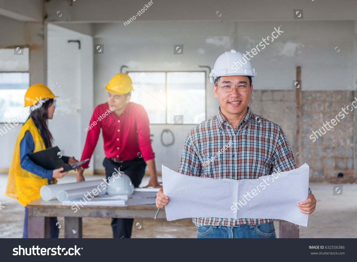 Group engineer checking blueprint on table stock photo 632556386 group of engineer checking the blueprint on the table and talking about construction project with commitment malvernweather Gallery