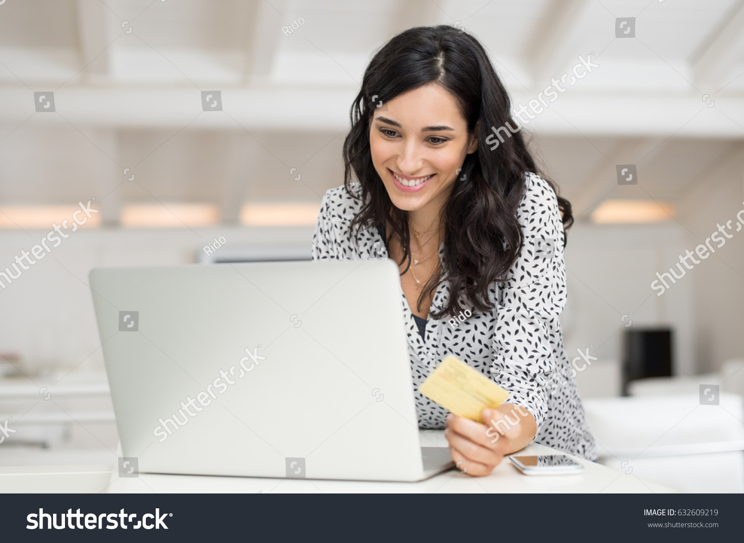 Happy young woman holding a credit card and shopping online at home   Beautiful girl using. Happy Young Woman Holding Credit Card Stock Photo 632609219