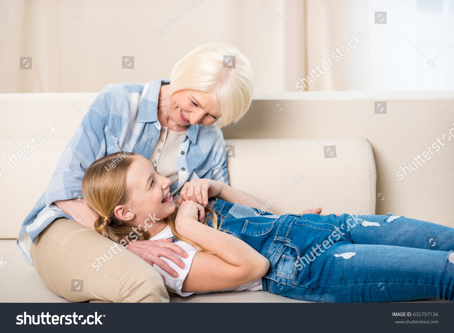 Happy Grandmother And Granddaughter Having Fun Together On Sofa