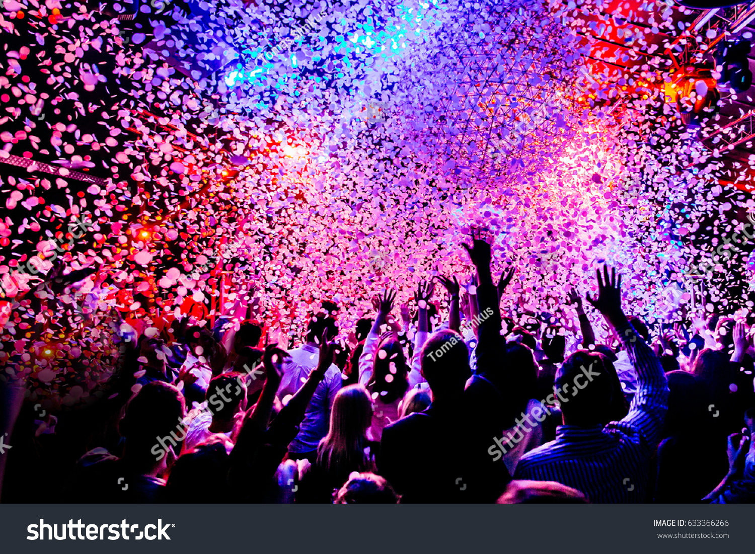 silhouettes of concert crowd in front of bright stage lights and confetti #633366266