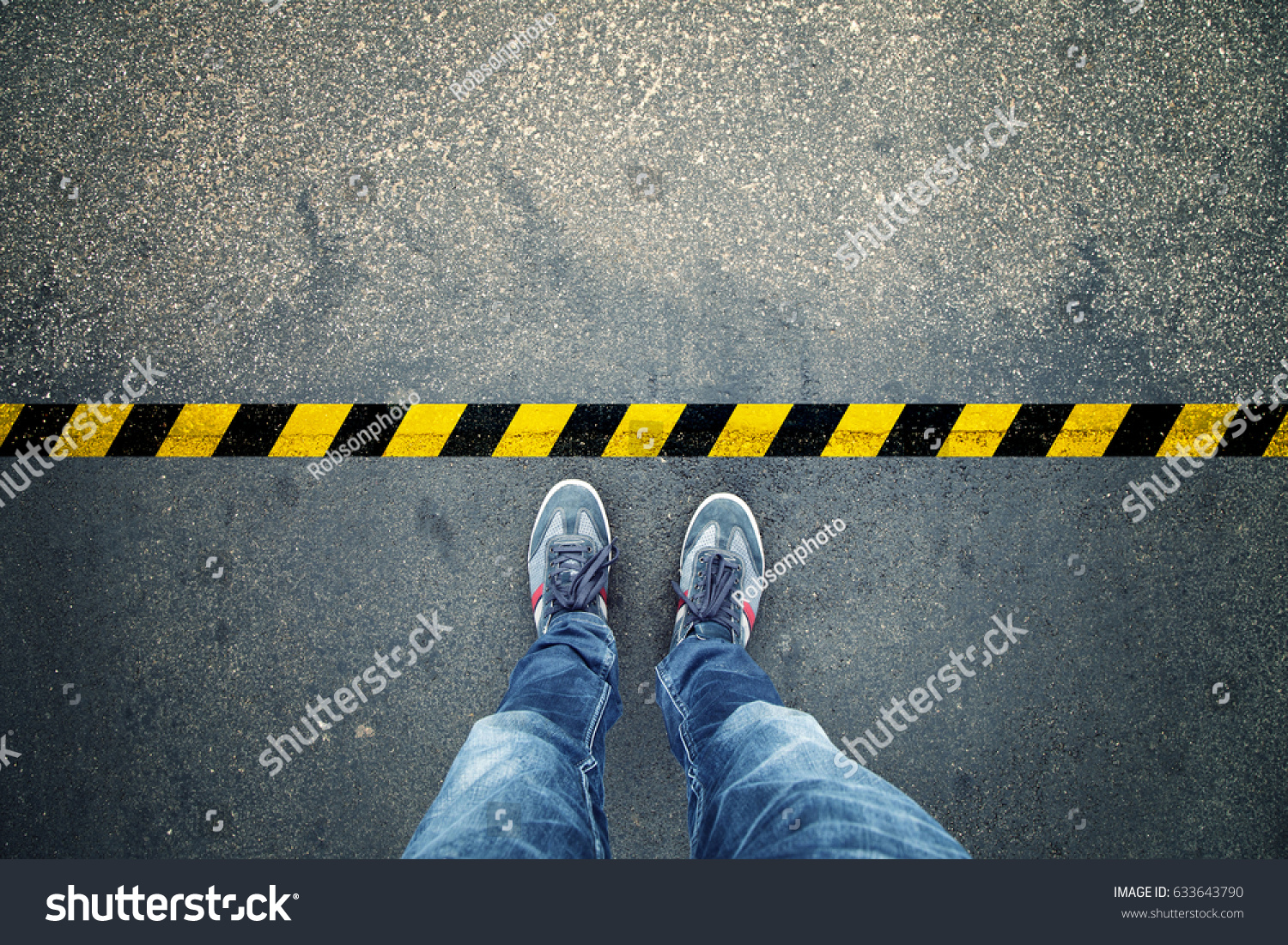 Top view of a man stands on industrial striped asphalt floor with warning yellow black pattern. #633643790