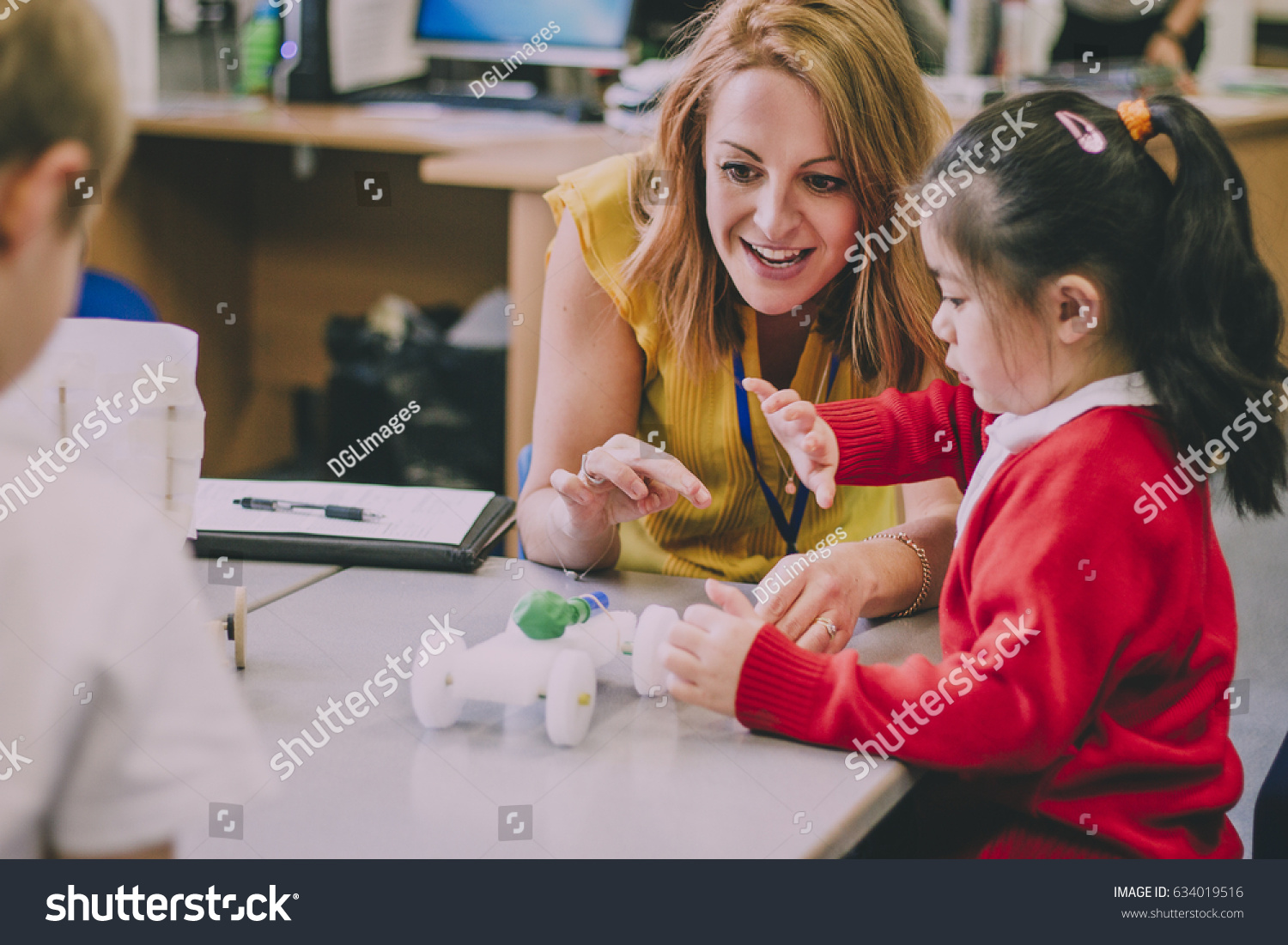 Teacher is sitting at the table in her classroom with her primary school students. They have built a car from recycled objects and crafts equipment and are testing that it works.  #634019516