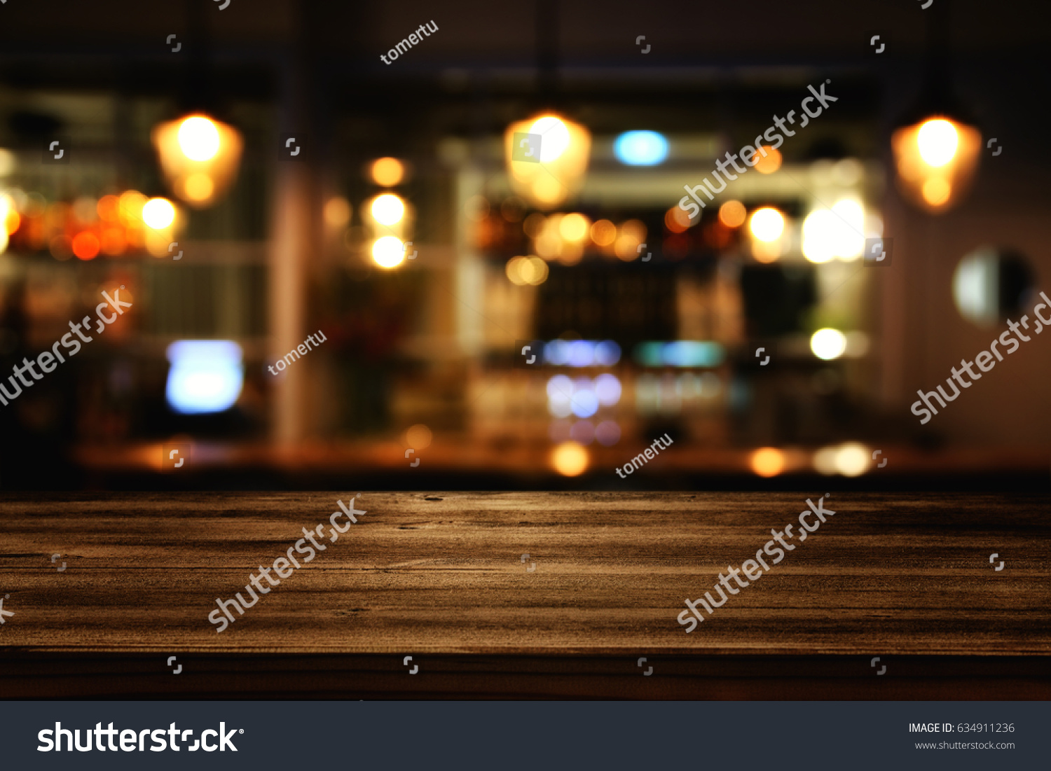Image of wooden table in front of abstract blurred restaurant lights background. #634911236