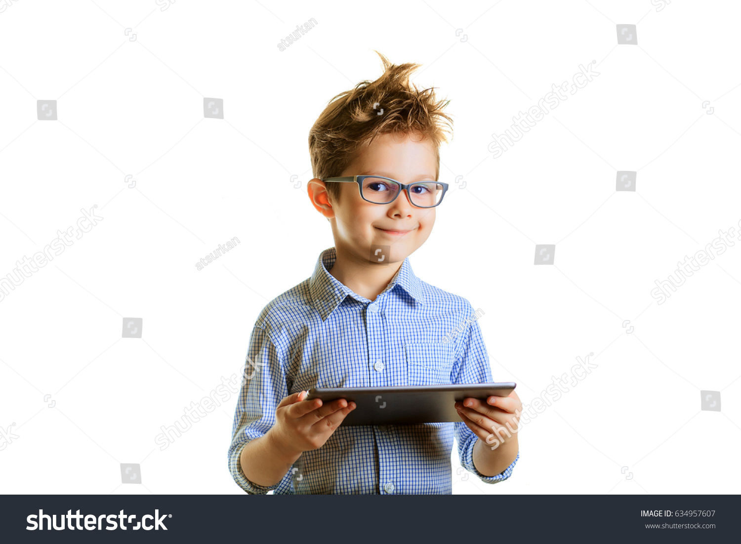 Portrait of a cute smiling boy using a tablet computer against a white background. Child in glasses with a laptop, isolated. Smart kid tells us about science.