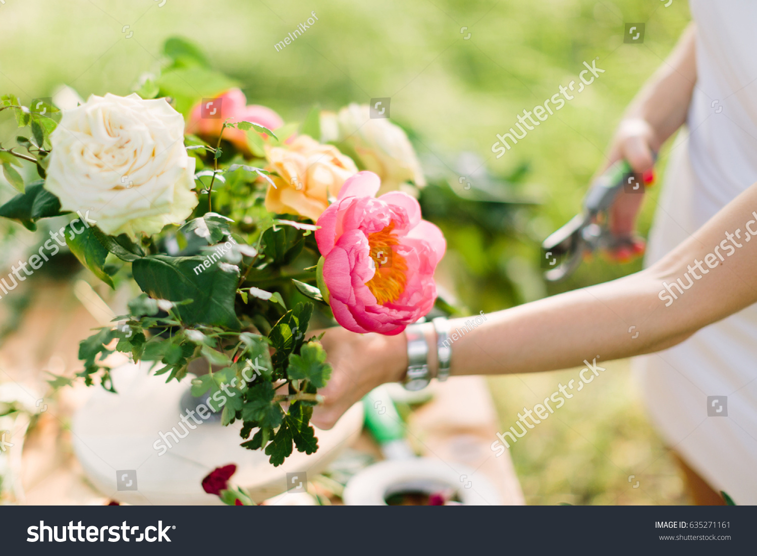 bouquet, people and floral arrangement concept - close-up on hands of young women decorating beautiful bouquet of fresh summer yellow and white roses, pink peonies, pruning shear in female hand #635271161