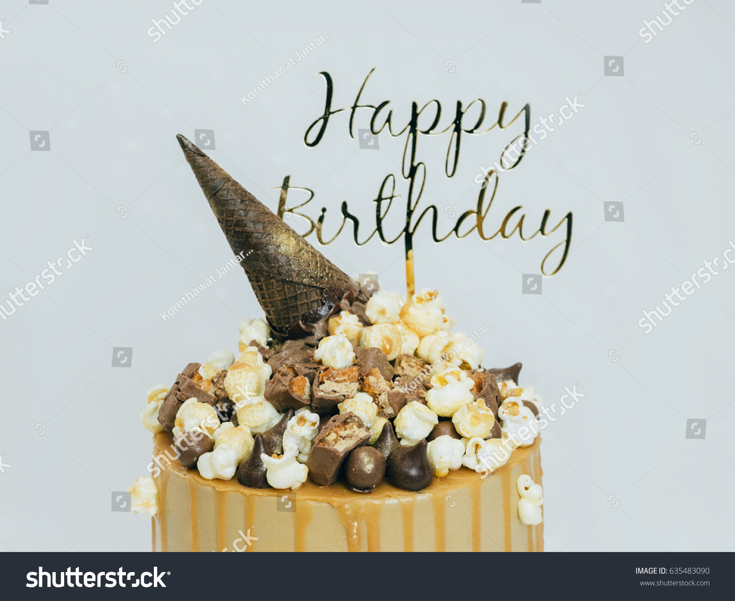 Yellow Cake Topping With Popcorn Caramel And Happy Birthday Sign Close Up