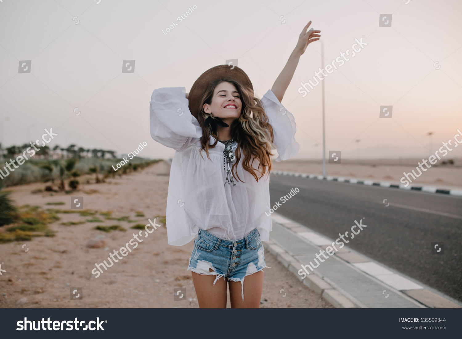 Smiling cheerful long-haired girl with curly hair breathes a full breast and enjoys freedom, standing next to road. Portrait of adorable young woman in white blouse and denim shorts having fun outside