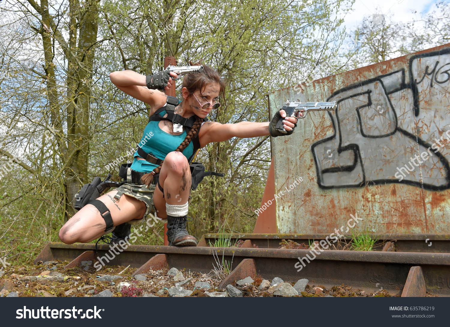 A young girl gets dressed up as a cosplay action woman. She poses outdoors  and