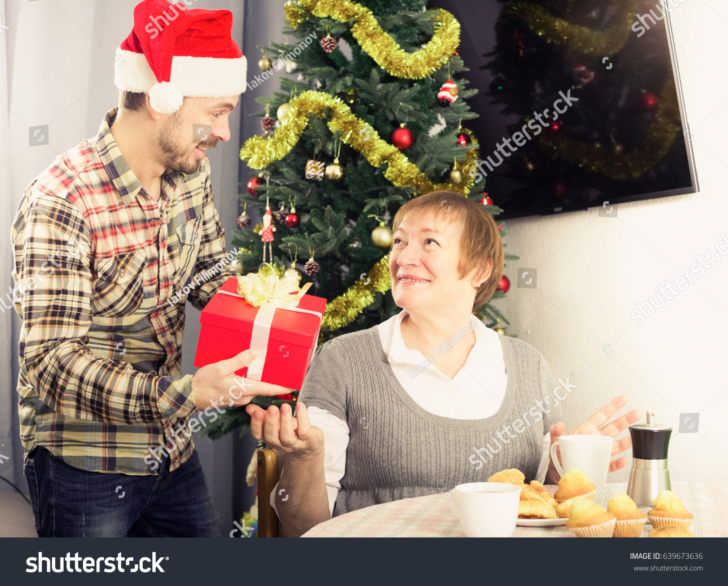 senior mother and son handing gifts to each other during christmas at home