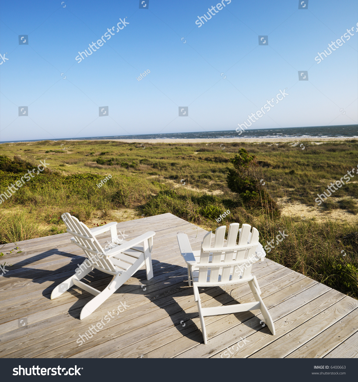 adirondack chairs on beach. Two Adirondack Chairs On Wooden Deck Overlooking Beach At Bald Head Island, North Carolina.