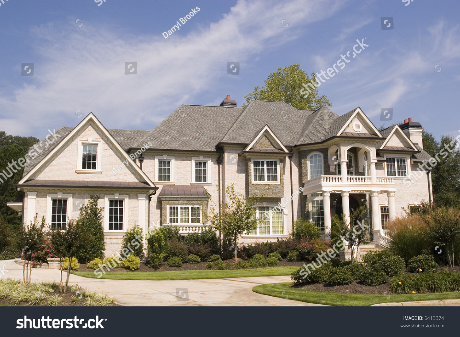 A nice grey brick house on a landscaped lot stock photo Nice house music