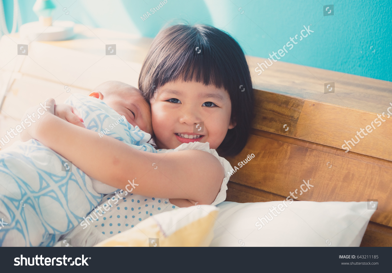 d3d4300fb8c3c Little Sister Hugging Kissing Her Newborn Stock Photo (Edit Now ...