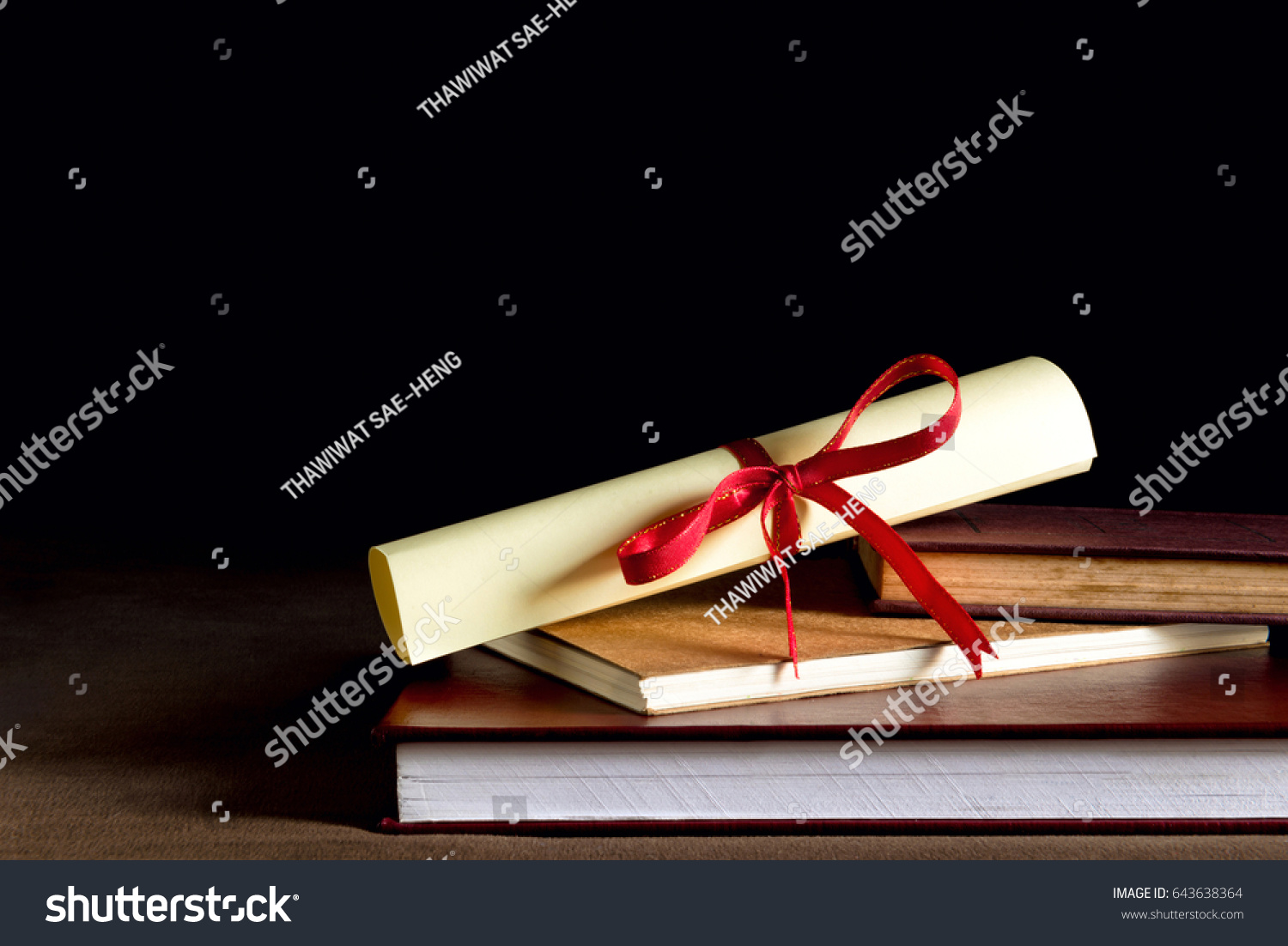 Scroll of certificate on top of the books with copy space , Back background #643638364