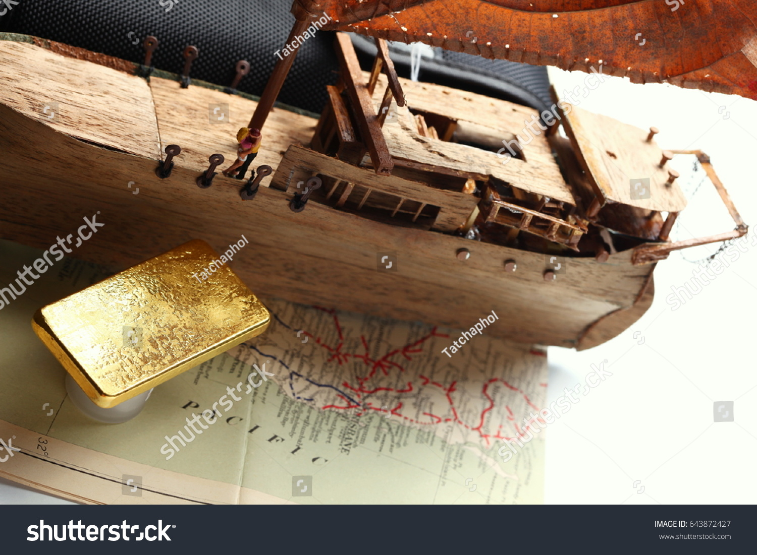 f2e747c17a05 Gold bar put beside miniature scratch build junk ship wooden model on the  old paper map