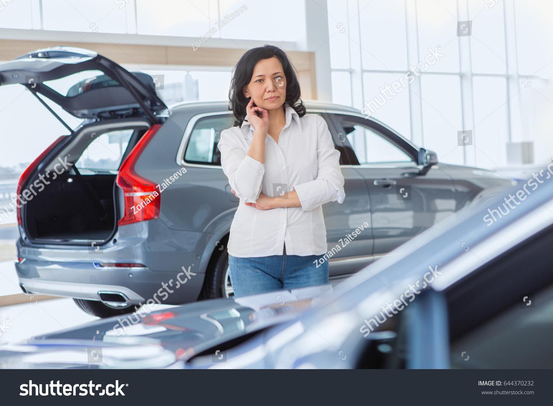 Thoughtful mature Asian woman choosing a car at the dealership. Female  customer thinking looking at