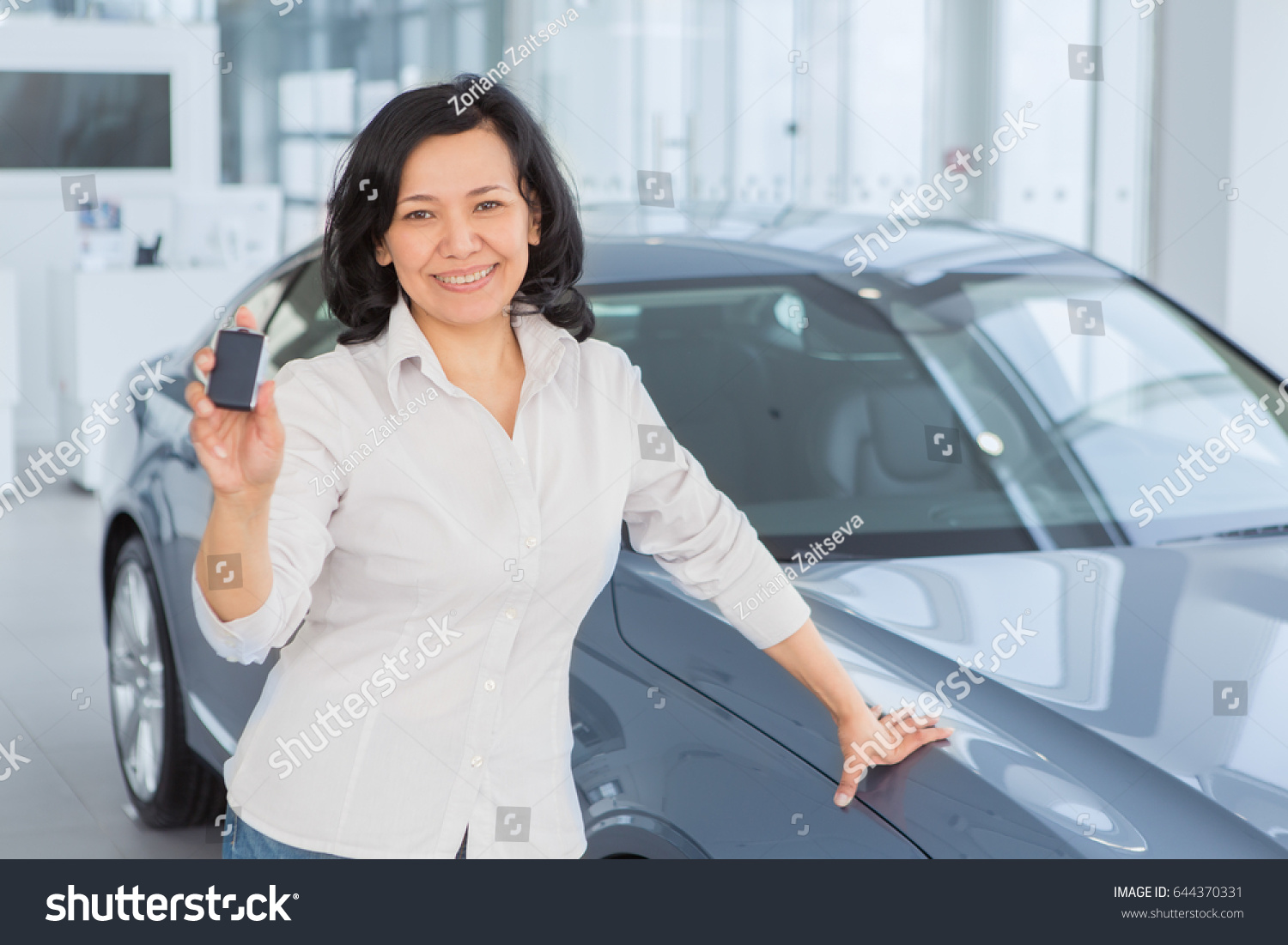 Happy mature Asian female smiling happily showing keys to her new car at  the dealership copyspace