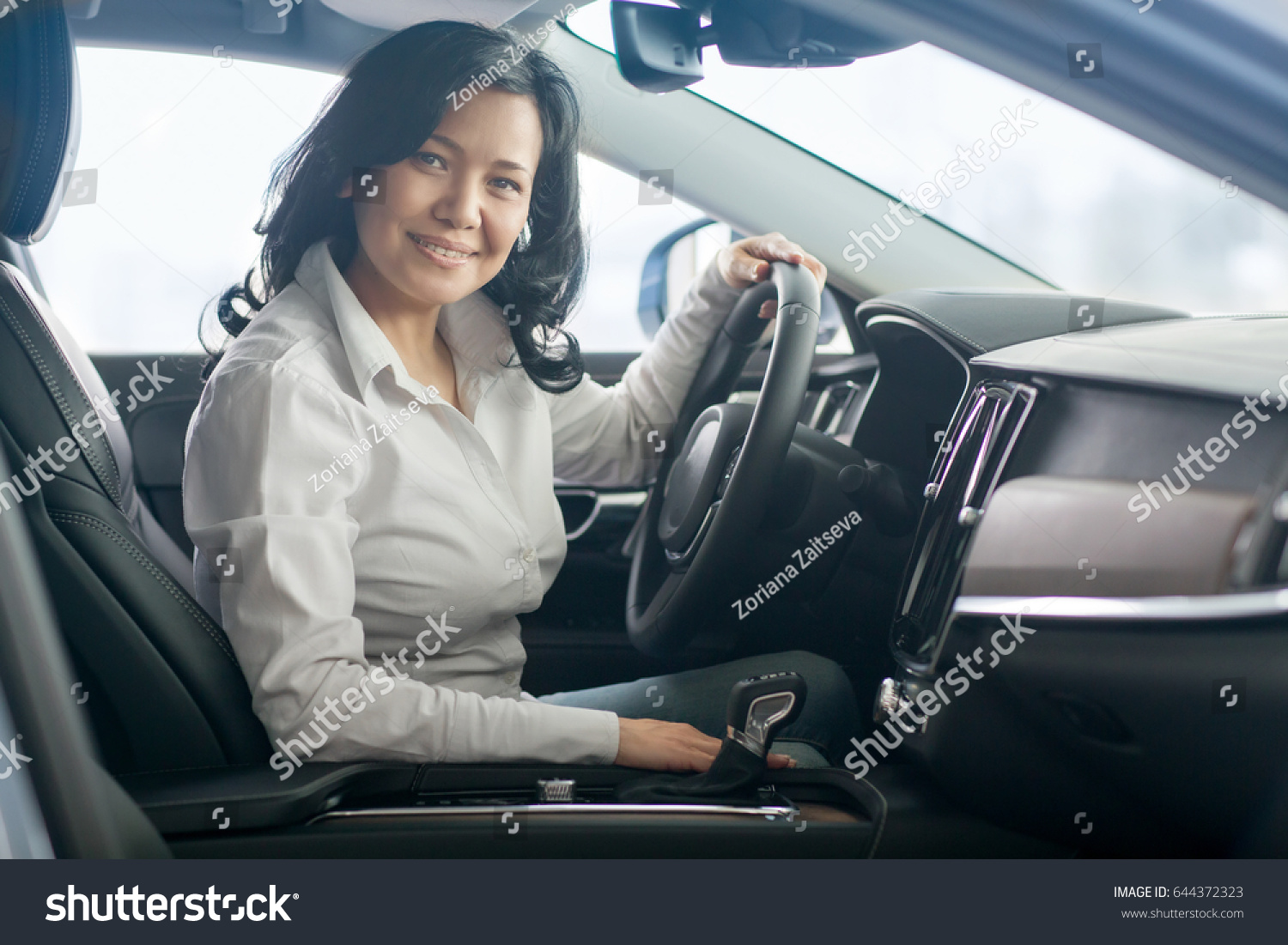 Happy mature Asian woman smiling to the camera joyfully sitting in a car at  the dealership