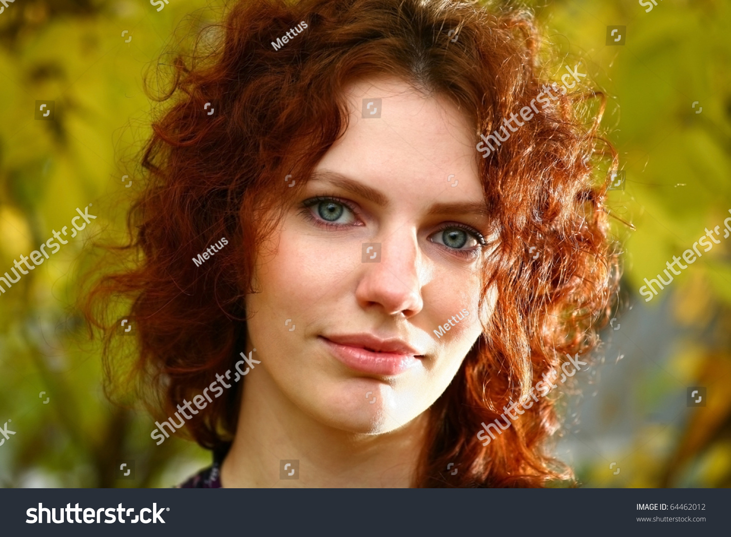 Ginger haired lady headshot backlit. A Beautiful Red-Haired Woman With A Curly Hairstyle Walking In The Park. Autumn Portrait Of A Calm Girl.