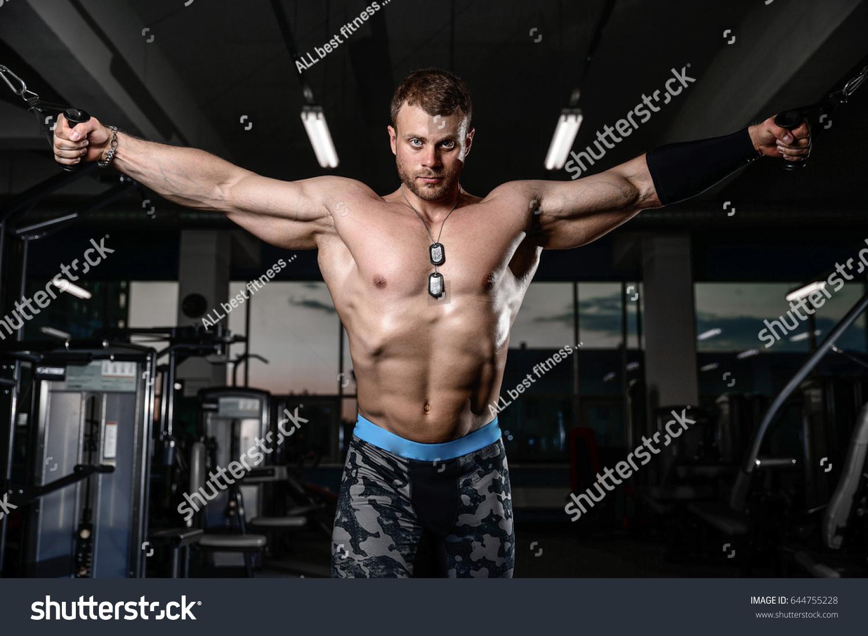 Brutalno močni atletski moški, ki črpajo mišice. Fotograf 644755228 - Shutterstock-2003