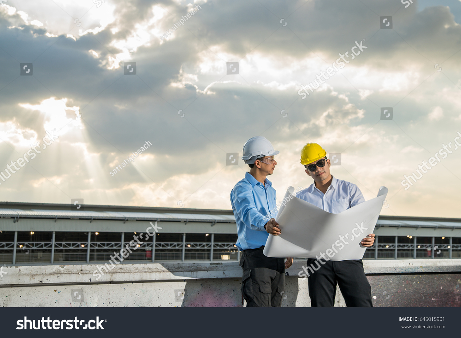 Young businessman engineer meeting looking blueprint stock photo young businessman and engineer meeting and looking blueprint paper on bright sky background future business malvernweather Choice Image