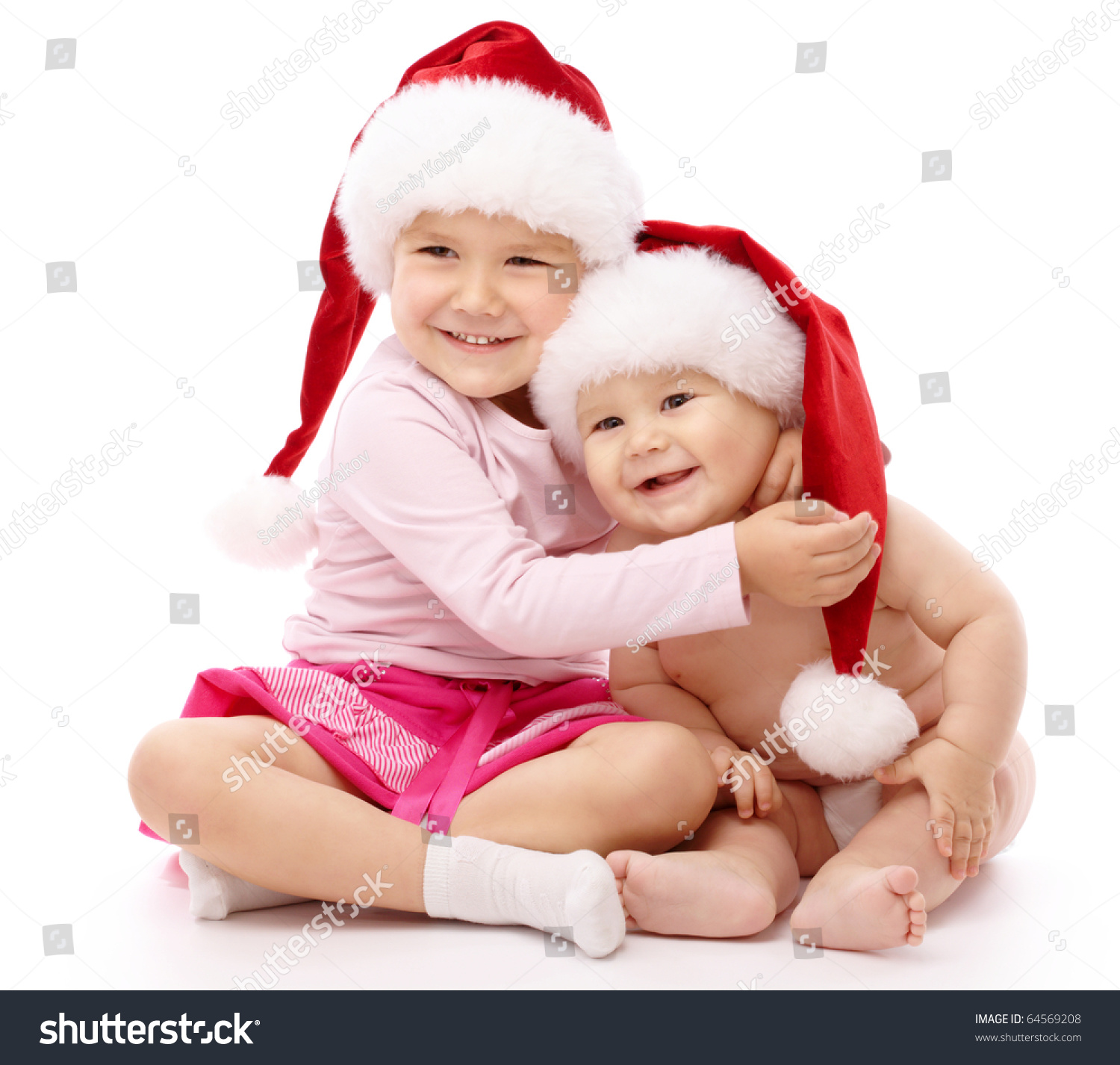 Girl hugs her little brother both wearing red christmas caps and