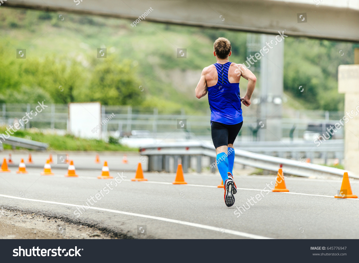 84eca9c375 male runner in compression socks running in road with traffic cones safety
