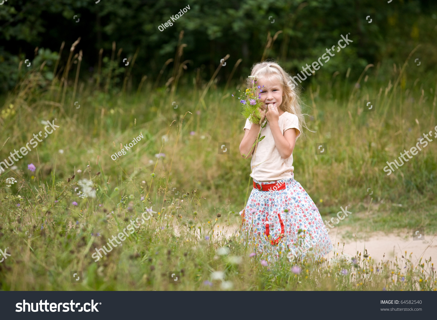 little blonde girl holding a bunch of wildflowers