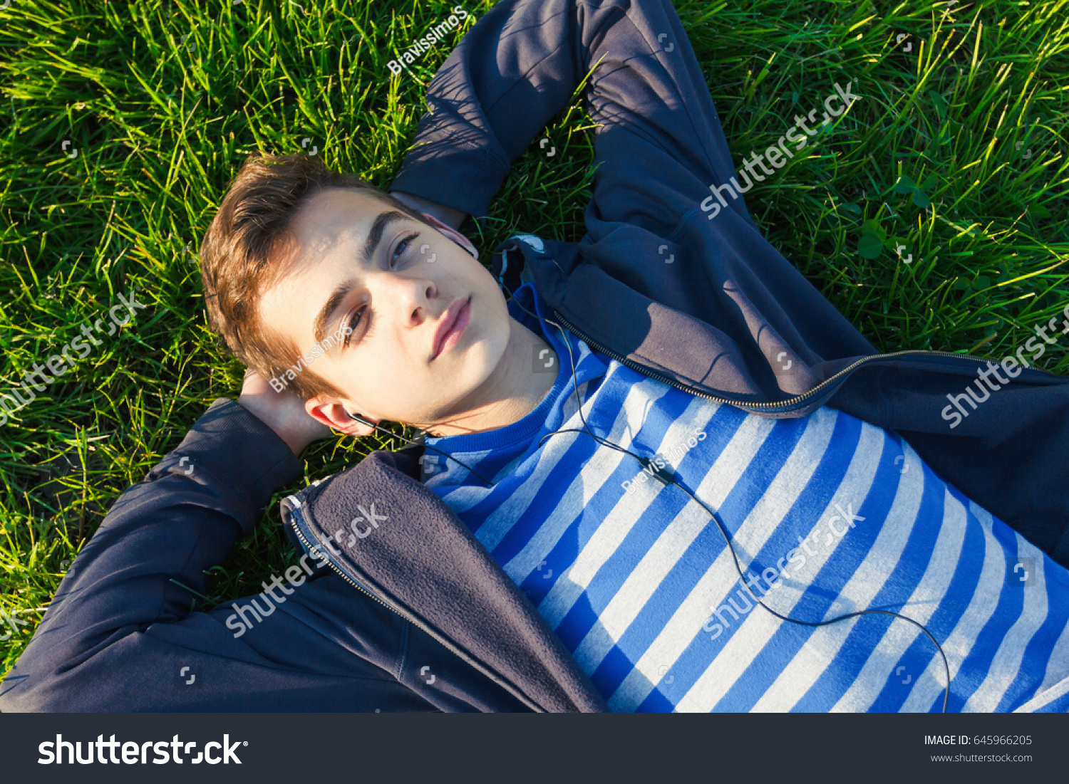Young man listening music from smart phone on the grass in the park