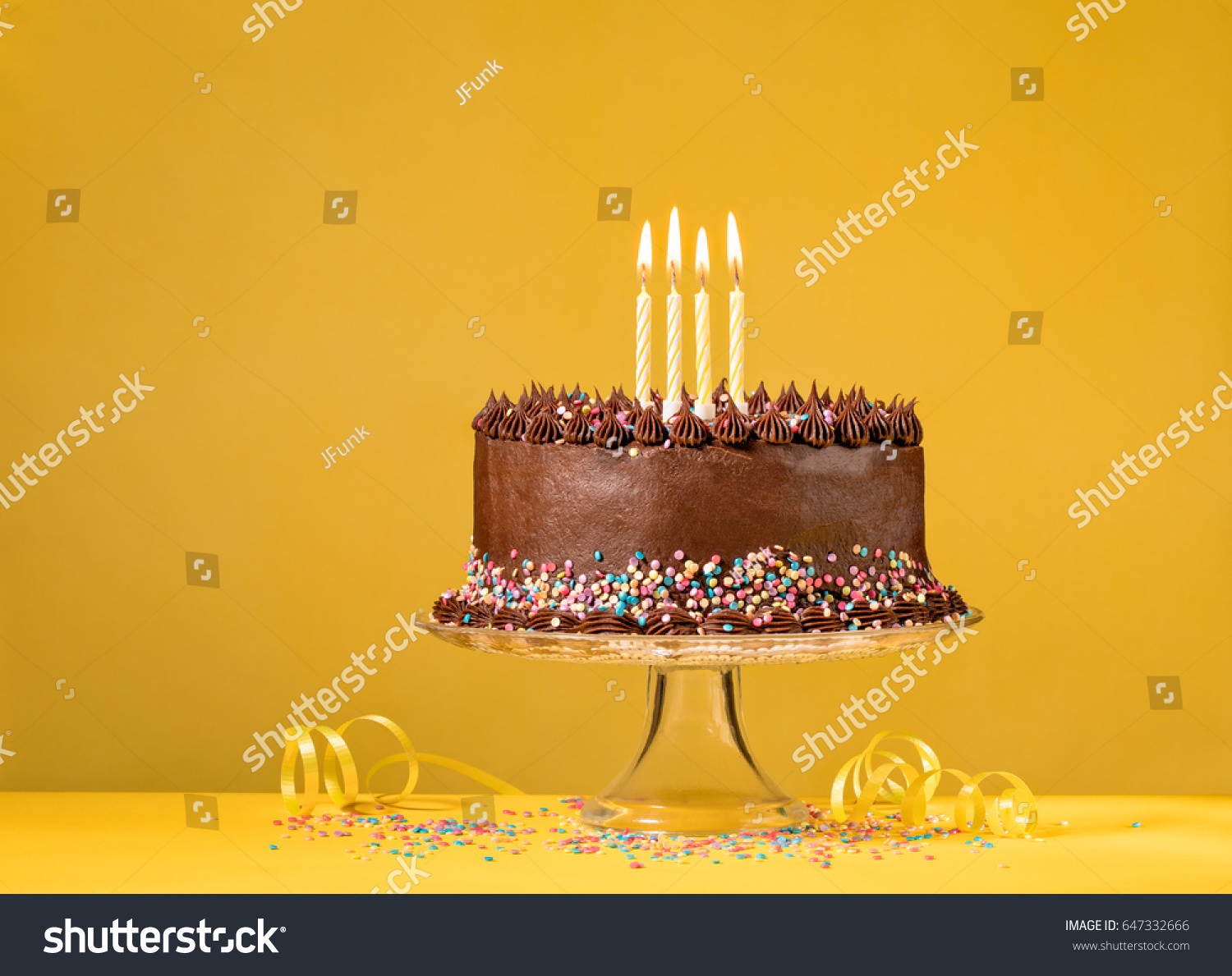 Chocolate Birthday Cake With Sprinkles And Candles Over Yellow Background