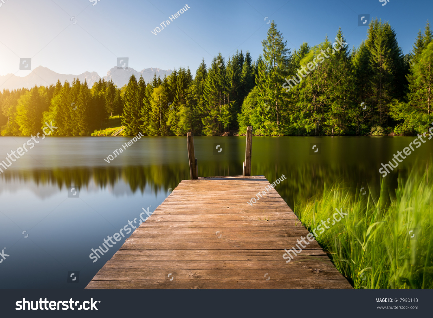 Idyllic view of the wooden pier in the lake with mountain scenery background. Alps in the early morning. #647990143