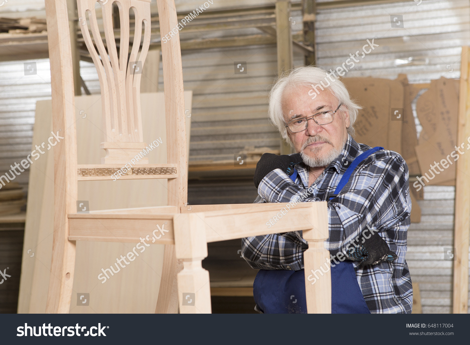 Serious furniture designer carefully polishes the chair frame, which he is busy manufacturing in his woodwork workshop, with shelves of wooden objects and patterns behind him #648117004