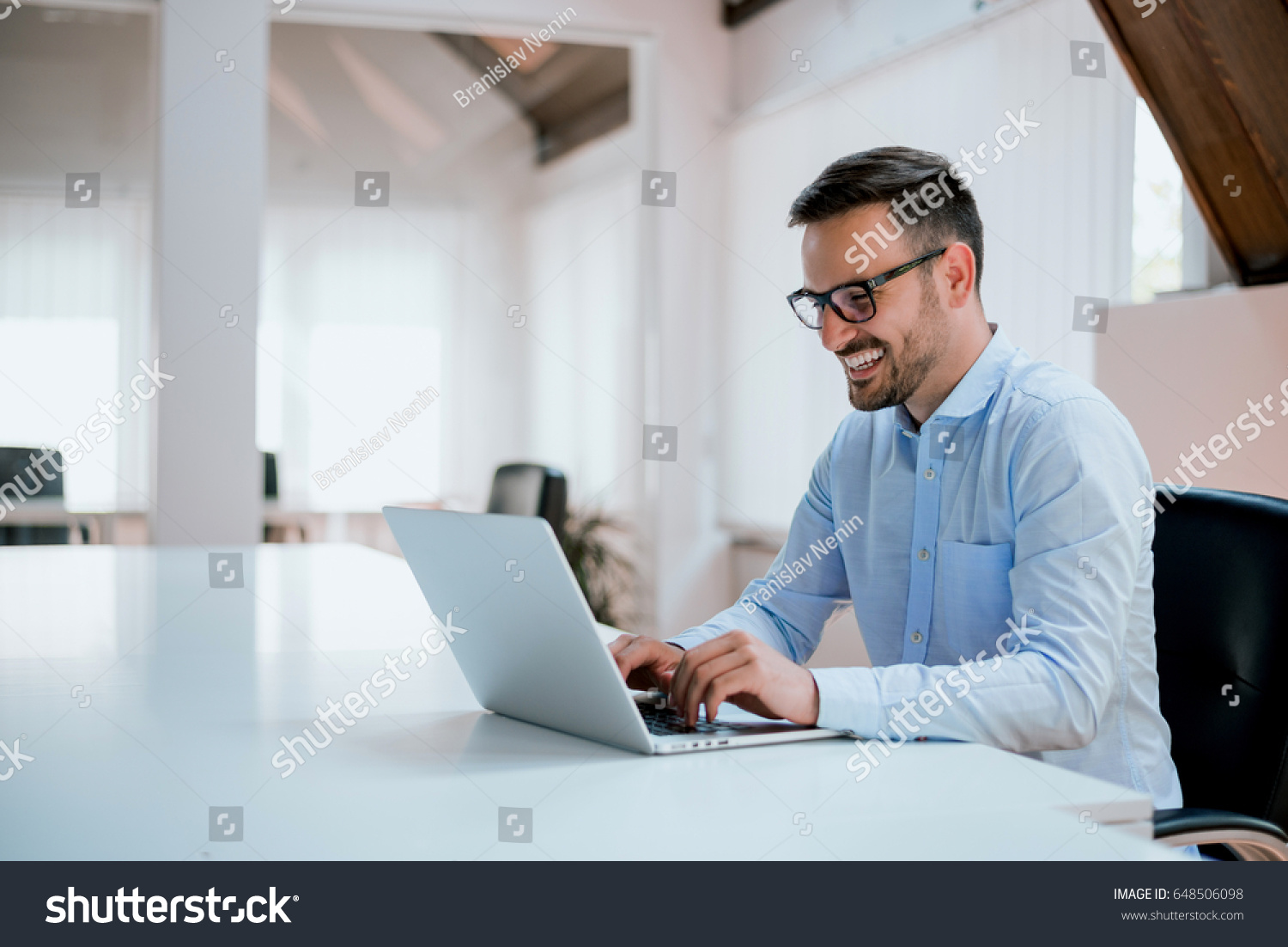 Portrait of young man sitting at his desk in the office #648506098