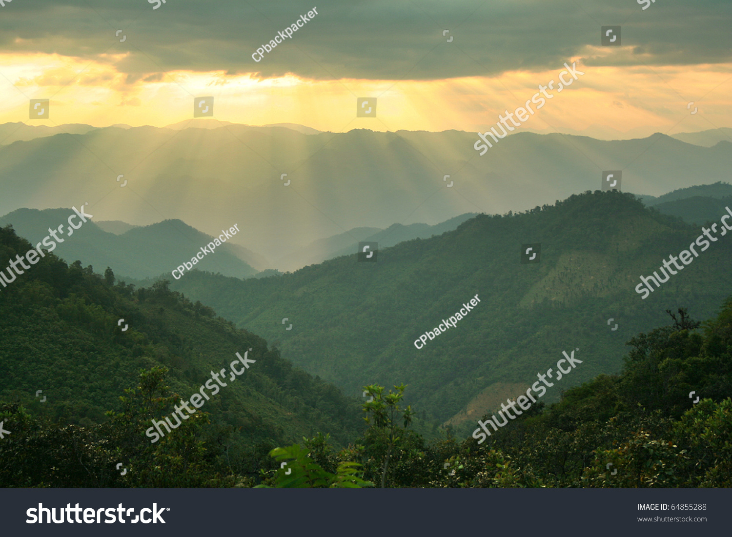 Sun shining through thick cloudy sky is golden light illuminating on the mountains. Located in Mae Ngao national park in Mae Hong Son province, northern of Thailand. #64855288