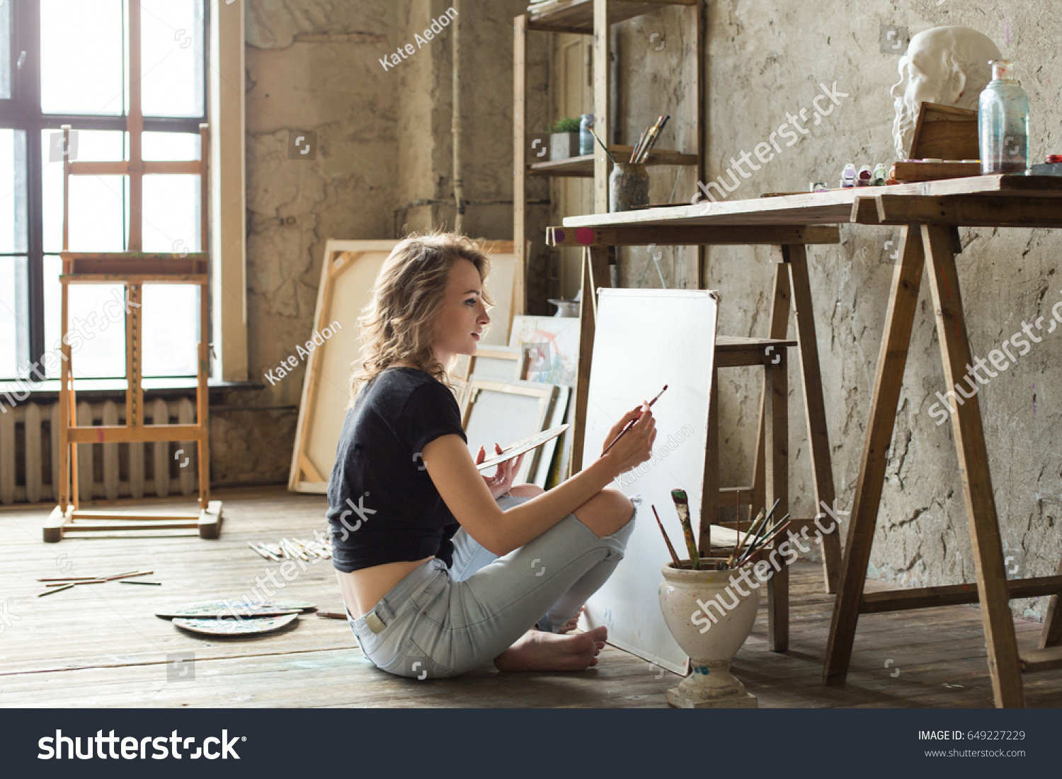Woman painter sitting on the floor in front of the canvas and drawing. Artist studio interior. Drawing supplies, oil paints, artist brushes, canvas, frame. Workshop or art class. Creative concept #649227229