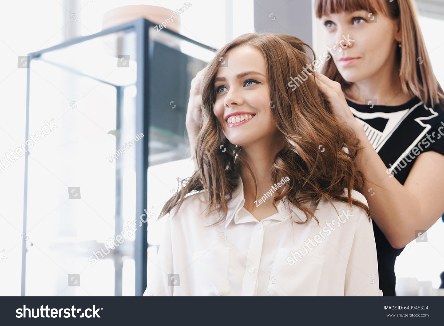 Closeup hairdresser makes hairstyle for young woman in beauty salon #649945324