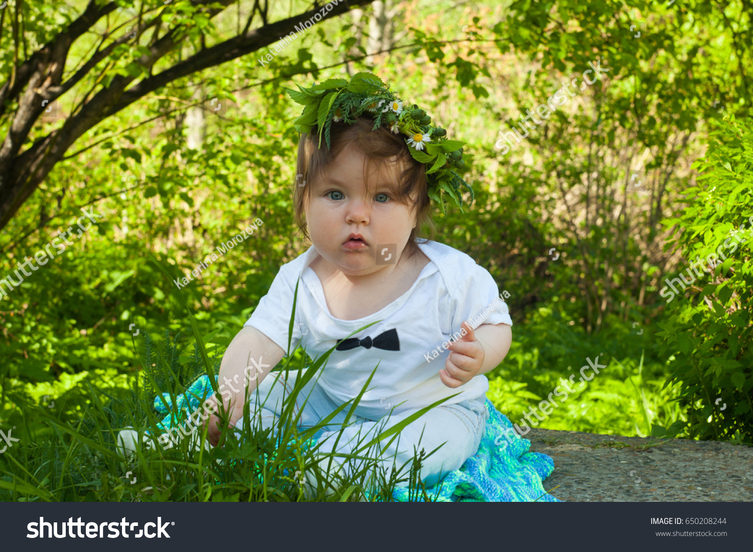 cute adorable nice baby girl or boy sitting in spring or summer park