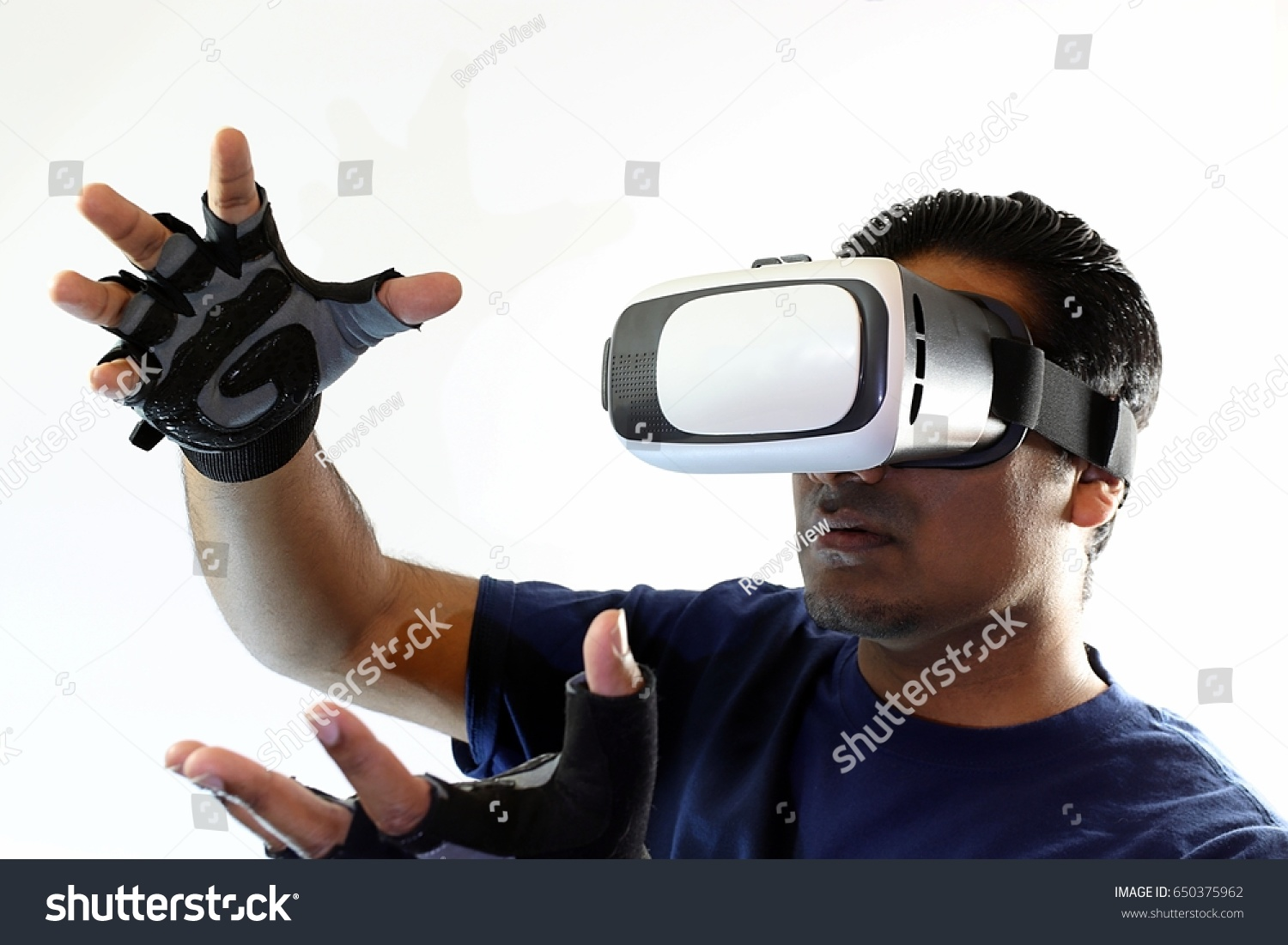 fbe0c0dd6448 Young handsome man wearing virtual reality goggles shaping object in hands  using controller gloves
