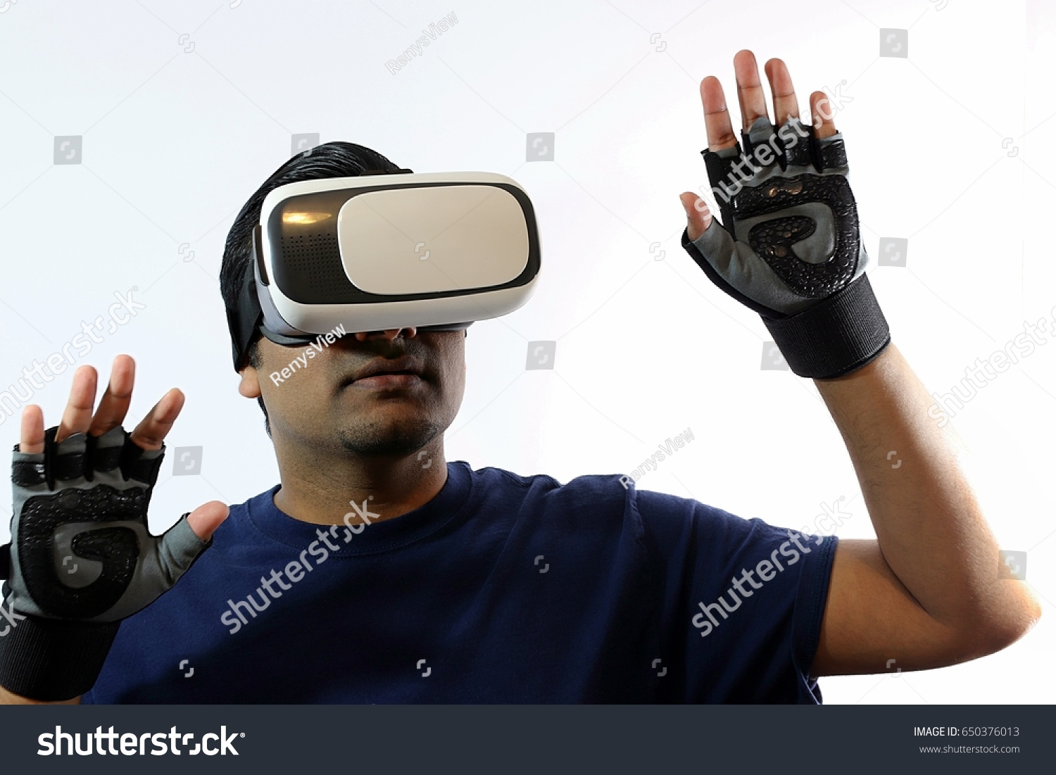 b03f164084d6 Young handsome man wearing virtual reality goggles with both arms up  wearing controller gloves