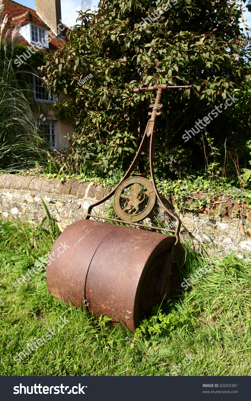 Garden Or Lawn Roller In Rusty Iron Left By Stone Wall With House