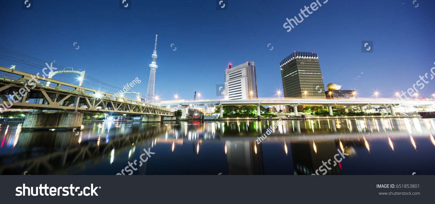 modern buildings near tokyo tower by river at night #651853801
