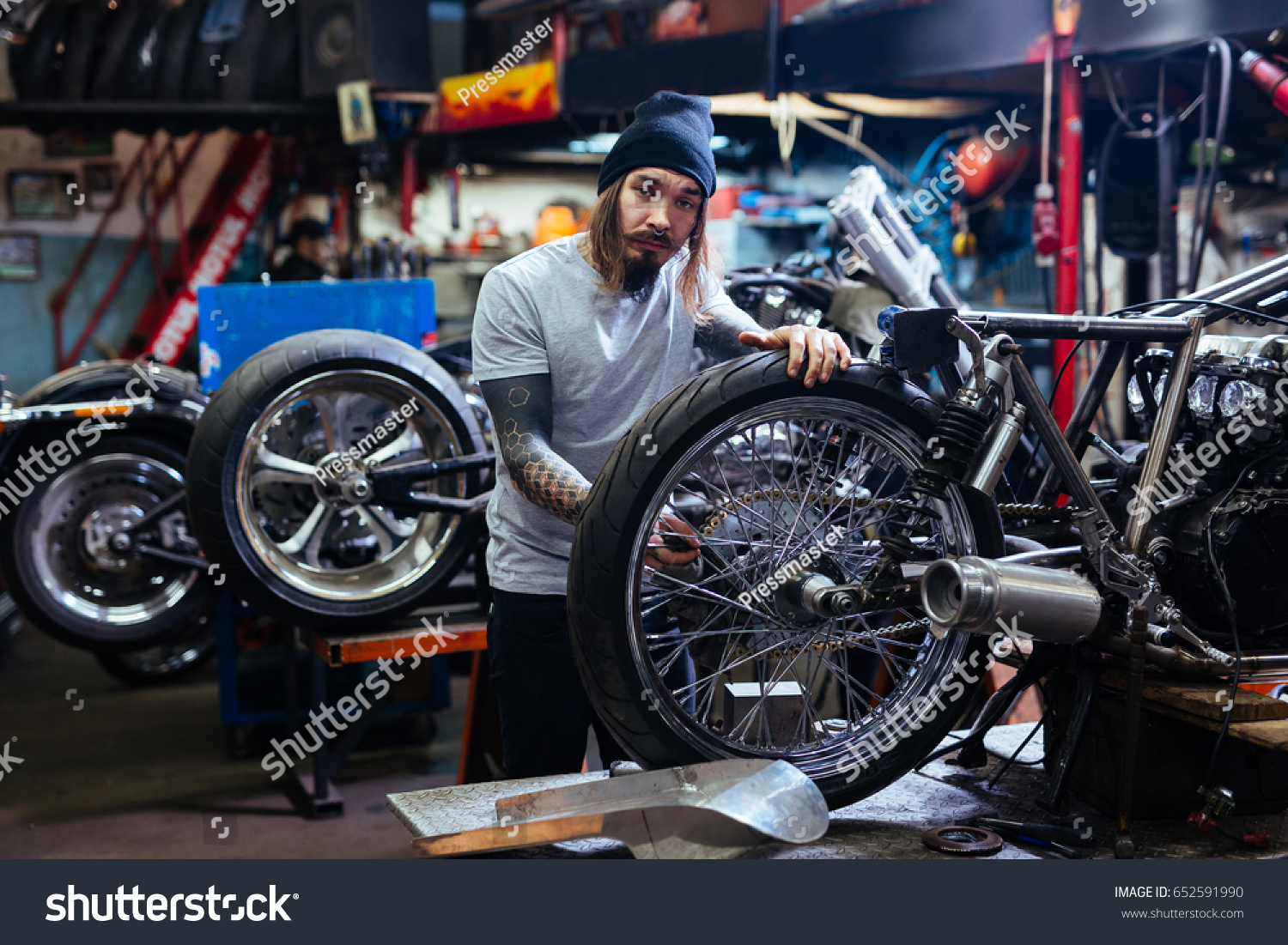 Portrait bearded tattooed man working garage stock photo for Garage tuning toulouse