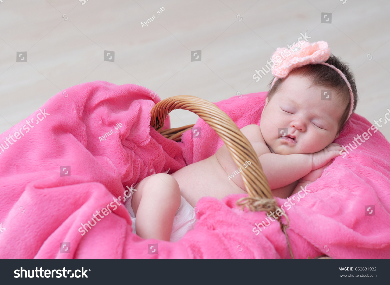 newborn sleeping basket baby girl lying stock photo (royalty free