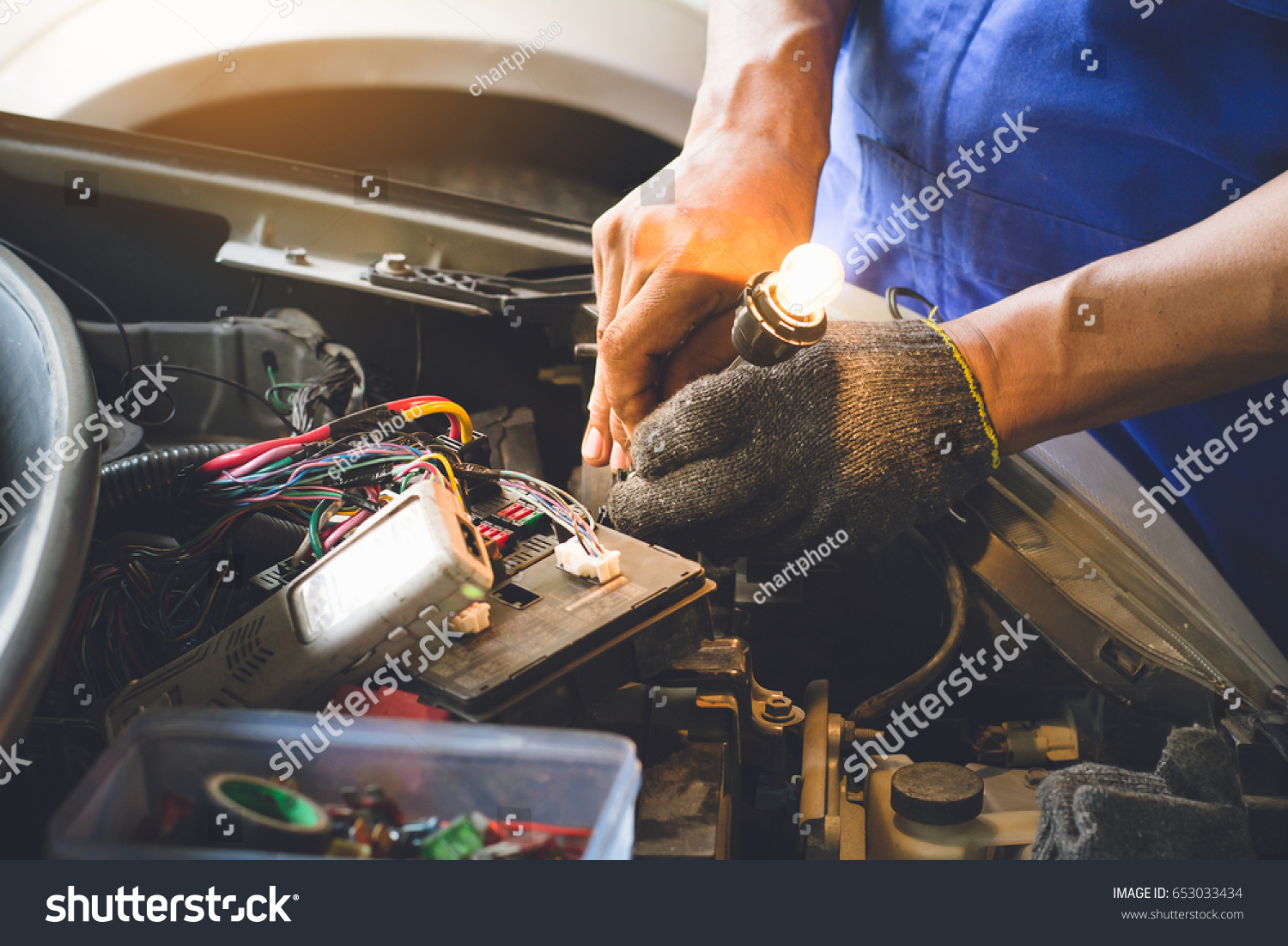 technicain checking car fuse by lamp tester which nagative pole of lamp  tester connected with car