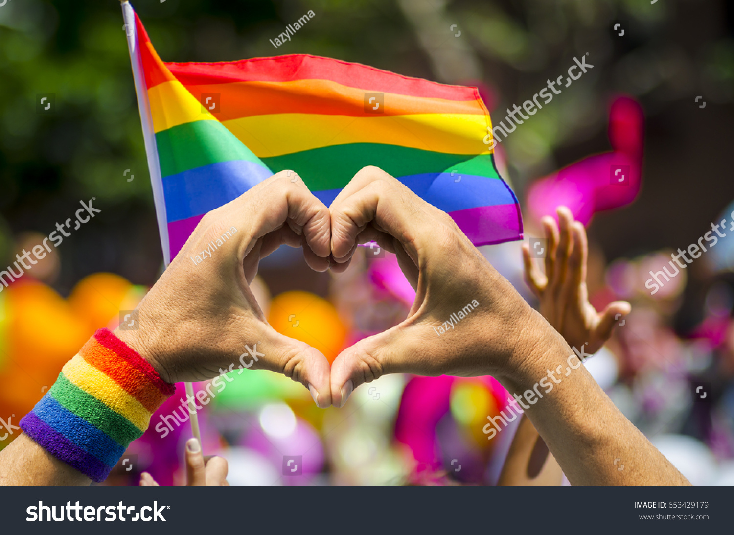Supporting hands make heart sign and wave in front of a rainbow flag flying on the sidelines of a summer gay pride parade #653429179