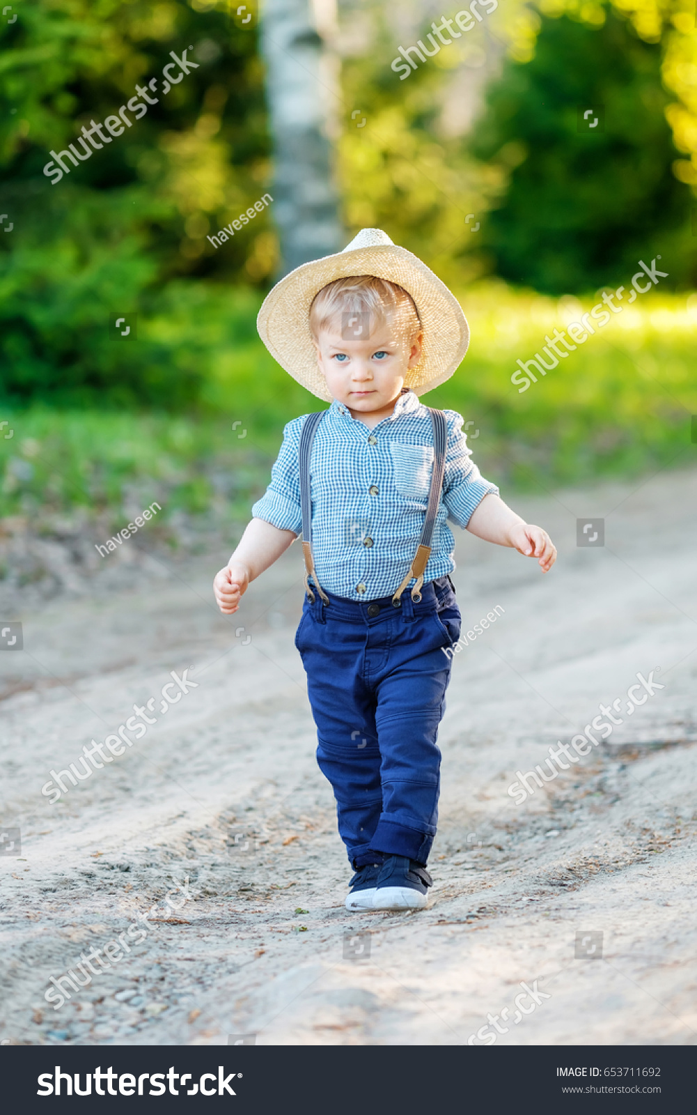 Portrait of toddler child outdoors. Rural scene with one year old baby boy  wearing straw hat 5f61c1037a2