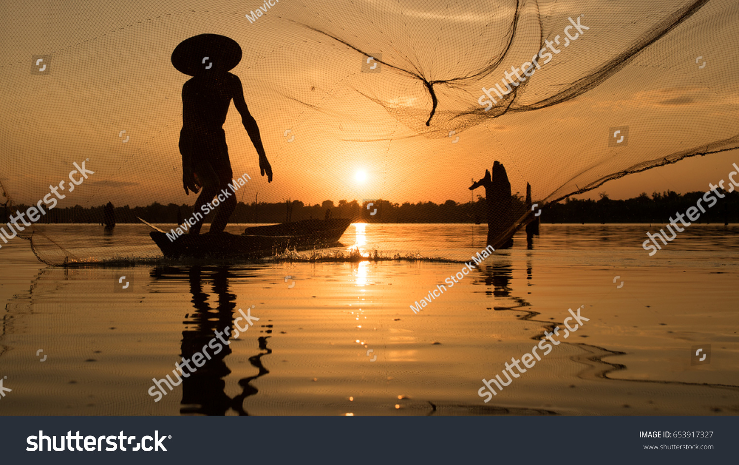 Fishermen using fishing nets.Silhouette fisherman on boat ,fishingman net, fishingman on boat, fisherman silhouette,fisherman boat, fishing with nets in the morning #653917327