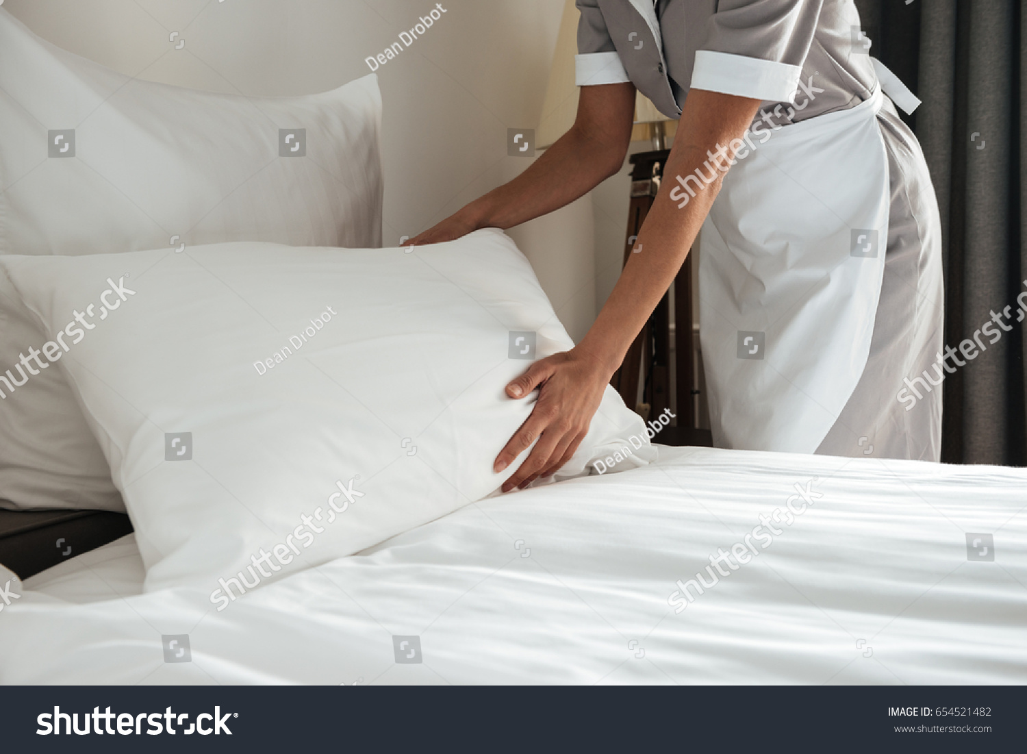 Cropped image of a female chambermaid making bed in hotel room #654521482
